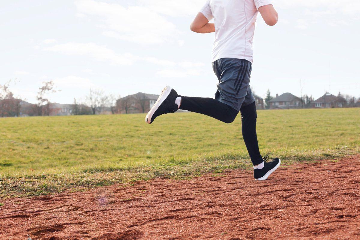 men's legs running on a field