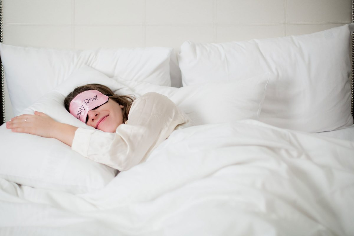 woman on white bed with eye mask